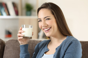 Woman holding a glass of milk looking at camera