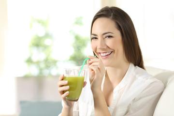 Woman drinking a vegetable juice looking at camera