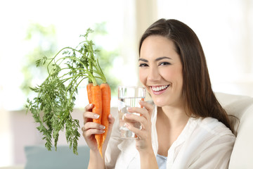 Woman holding carrots and a water glass looking at camera