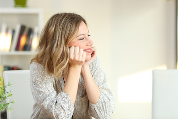 Pensive happy homeowner looking at side at home