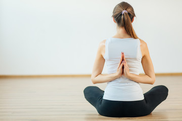 woman practicing yoga with namaste behind back, sitting on floor, vajrasana pose, indoor, rear view