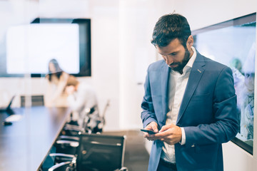 Portrait of businessman using phone in office