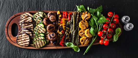 banner . a large wooden tray with a Summer snack, colorful Barbecue Vegetables, cherry tomatoes and greens. summer delicious healthy food for a big company of people or friends