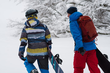 Two happy snowboarders is walking, talking and laughing