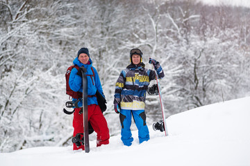Two joyful snowboarders rest among snow covered trees