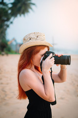 young red-haired woman photographer taking a picture on the beach at sunset