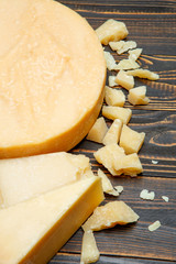 Head of parmesan or parmigiano hard cheese and pieces on wooden background