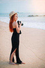 young red-haired woman standing by the ocean with a camera in her hands and looking at the sunset