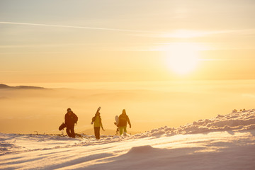 Three friends with ski and snowboards at sunset mountains