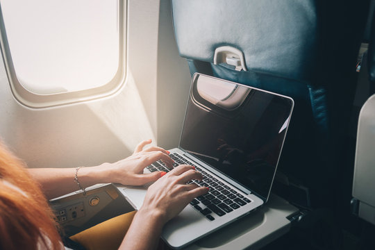 young red-haired woman uses laptop while flying on airplane near window, close-up