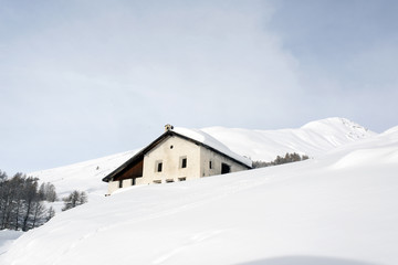 A village house in the snow covered hill in the alps switzerland in winter