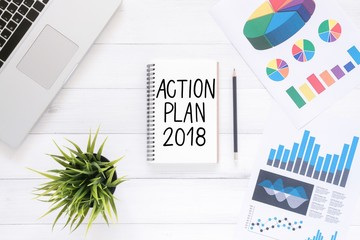 Minimal Work space - Flat lay view photo of working desk with a business action plan of a new year notebook and laptop on white wooden background. Top View flat lay photography. New year 2018 concept