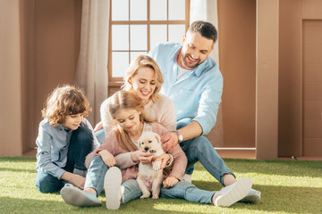 beautiful young family with yellow lab puppy on yard of cardboard house