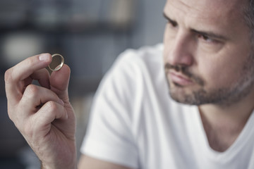 Disappointed man holding wedding ring