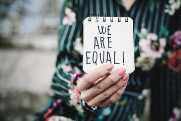 woman shows notepad with the text we are equal