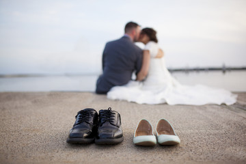 Bride and groom shoes with couple out of focus kissing in background