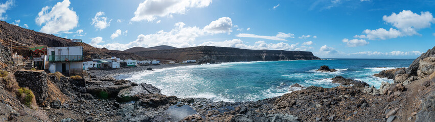 panoramic shot of small fishing village in wild coastal scenery on canary islands under blue sky