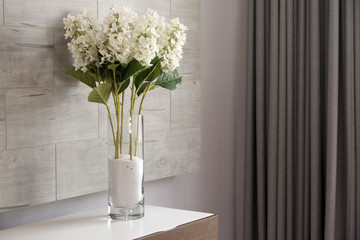 Bouquet of white flower in a vase on a table in room corner