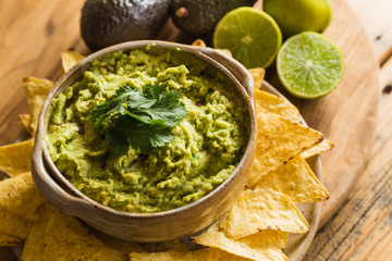 Bowl of guacamole dip and tortilla chips with limes and avocados