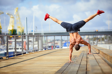Athletic man doing a handstand exercise during an outdoors workout in the city