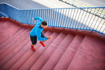 Top view of an athletic man jogging on stairs during an outdoors workout in the city