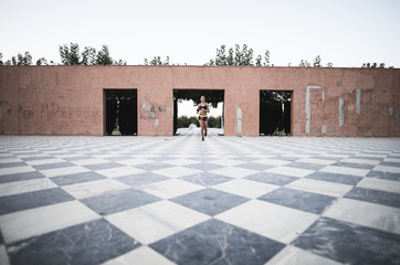 Athlete woman running on park chess floor