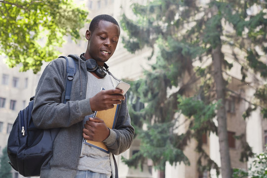 Happy african-american student texting in university campus