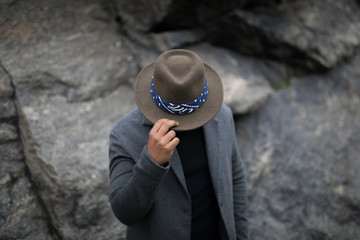 A man hides his face with a hat