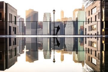 Reflection of man and cityscape in water Wall mural