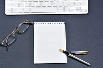 Notepad with fountain pen, eyeglasses and keyboard computer