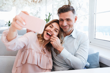 Image of young and beautiful couple making selfie and having fun together, while having date in restaurant