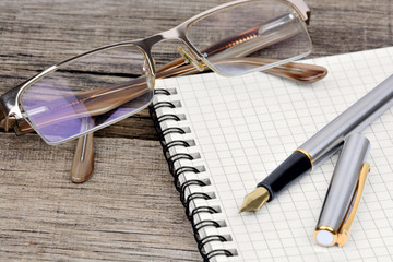 Notebook with fountain pen and eyeglasses on table