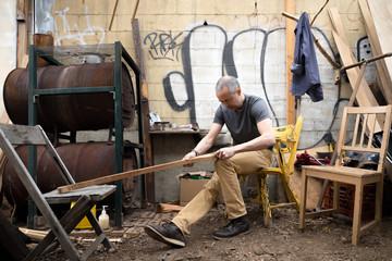 Man carving a boat oar