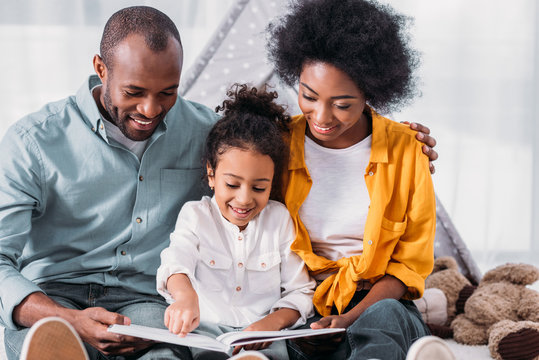 happy african american daughter reading for parents at home