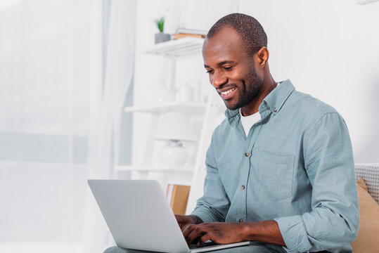happy african american man using laptop on sofa at home