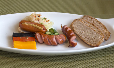 Three cheeses with the colors of the German flag and a mini-sandwich - bread with mayonnaise and wurst with Bavarian mustard and vegetables.