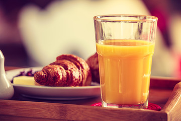 Breakfast on little table, orange juice croissant