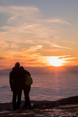 Couple on mountain looking over low stratus to beautiful sunset