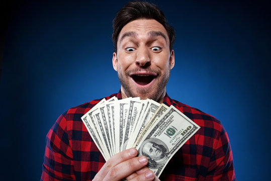 Handsome bearded man in red shirt. Funny guy is a lucky winner, she is holding a pile of money, he is surprised and can't believe it, he is happy to win one million dollar jackpot, now he is rich.