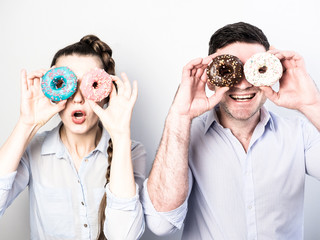 Funny and in love couple with colorful donuts on a background a white wall. Pink, blue, white and brown colors.