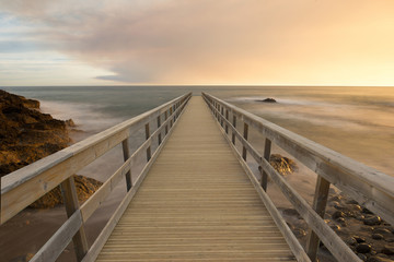 Wooden walkway in the sea at sunset