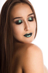 Beautiful young model with perfect skin and creative metallic green makeup. Closeup portrait at studio on a white background
