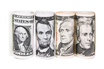 vier gerollte dollarscheine vor weßem hintergrund