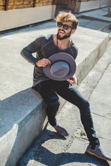 Happy hipster man holding hat in the street