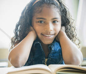 Portrait of smiling mixed race girl reading book
