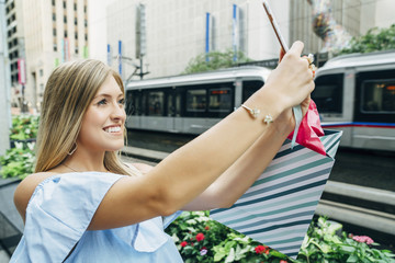 Caucasian woman with shopping bag posing for cell phone selfie