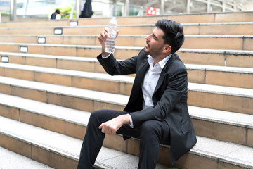 Happy businessman showing water bottle at stairs outdoors.