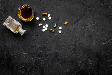 Hungover syndrome. Alcoholism. Glass and pills on black background top view copy space