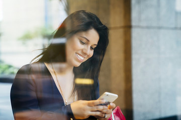 Smiling Hispanic woman texting on cell phone
