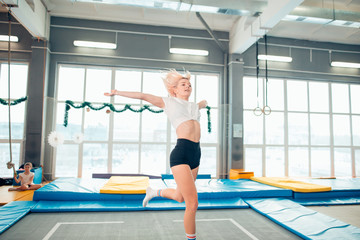 Twine young woman jumping on trampoline club